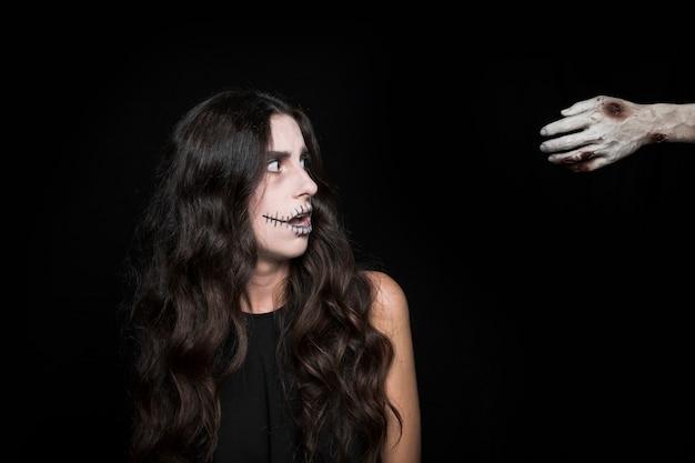 Mujer sorprendida mirando la mano muerta