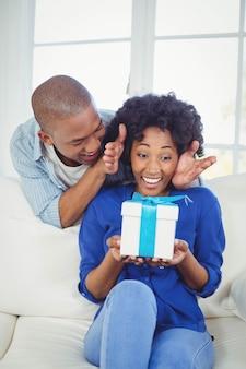 Mujer sorprendida mirando el regalo en sus manos en el sofá