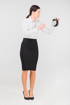 Mujer sorprendida mirando el reloj de alarma en la mano