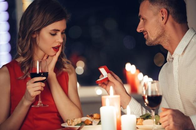 Mujer sorprendida mirando a su hombre dando su caja con anillo de compromiso