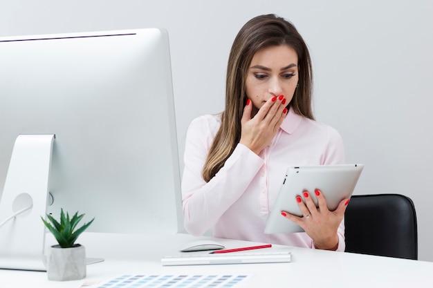 Mujer sorprendida mirando su tableta y cubriendo su boca
