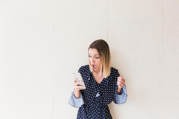 Mujer sorprendida mirando teléfono móvil