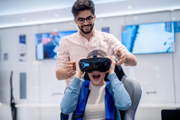 Mujer sorprendida mirando a través de gafas de realidad virtual mientras está sentado en el asiento interactivo de realidad virtual. hombre de pie a sus espaldas.