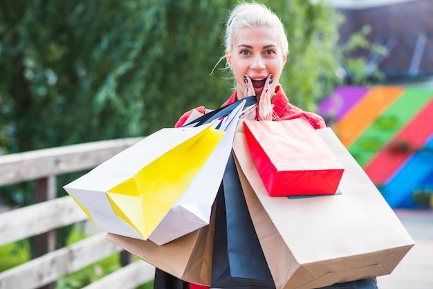 Mujer sorprendida con paquetes de compras.