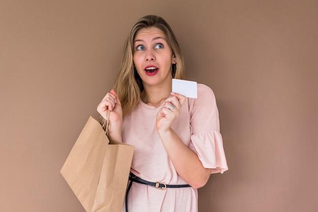 Mujer sorprendida de pie con bolsa y tarjeta de crédito