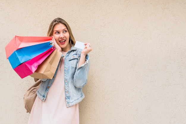 Mujer sorprendida de pie con bolsas de compra y tarjeta de crédito en la pared