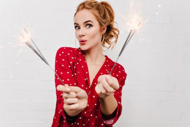 Mujer sorprendida en pijama rojo posando con bengala. señora rubia linda en traje de noche divertido con luces de bengala en la mañana de navidad.