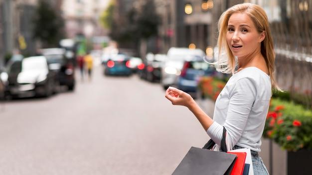 Mujer sorprendida posando sosteniendo bolsas de compras al aire libre