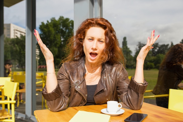 Mujer sorprendida positiva que se sienta en cafetería al aire libre