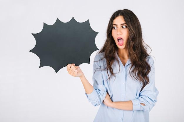 Mujer sorprendida presentando pizarra de burbuja de texto