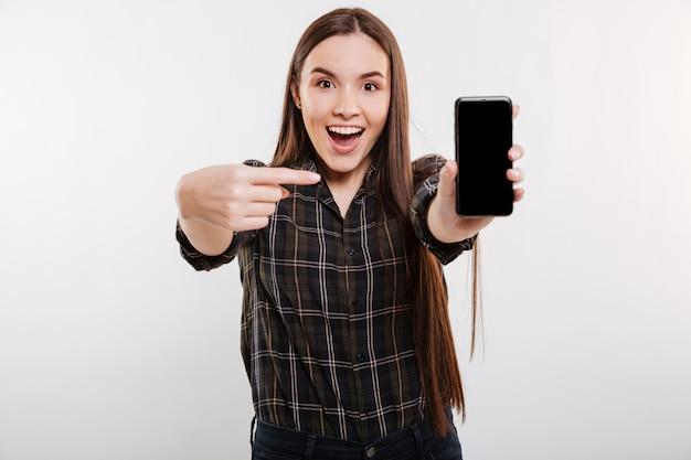 Mujer sorprendida que muestra la pantalla del teléfono inteligente en blanco