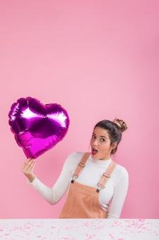 Mujer sorprendida que sostiene el globo del corazón en la mano