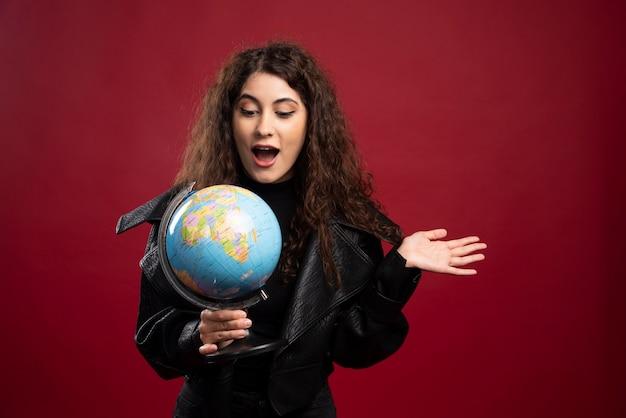 Mujer sorprendida que sostiene el globo.