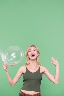 Mujer sorprendida que sostiene los globos