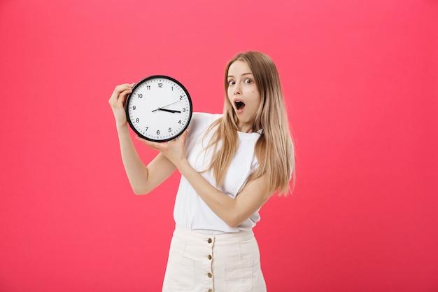 Mujer sorprendida que sostiene el reloj. sorprendida mujer en camiseta blanca sostiene reloj negro