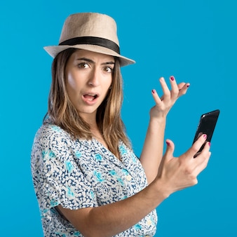 Mujer sorprendida que sostiene el teléfono
