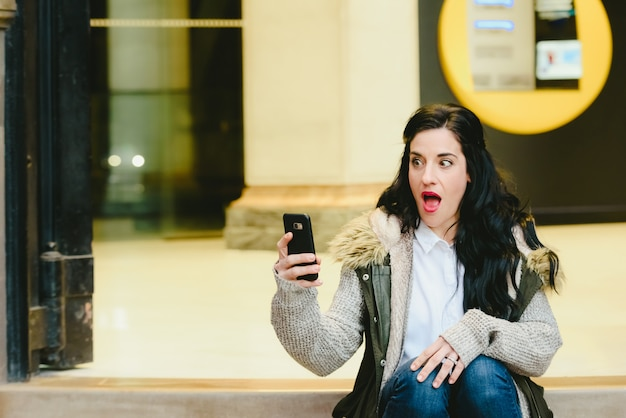 Mujer sorprendida de recibir buenas noticias por su teléfono móvil.