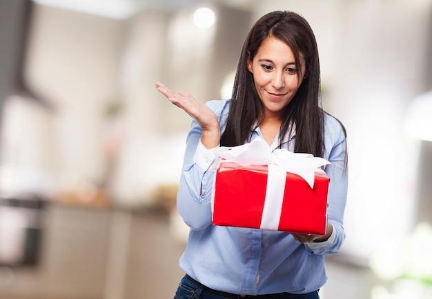Mujer sorprendida con un regalo rojo