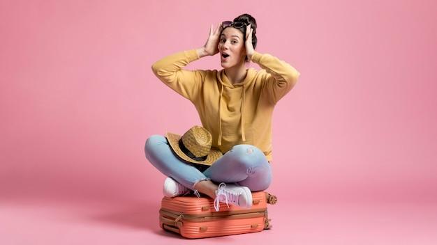 Mujer sorprendida sentada en el equipaje