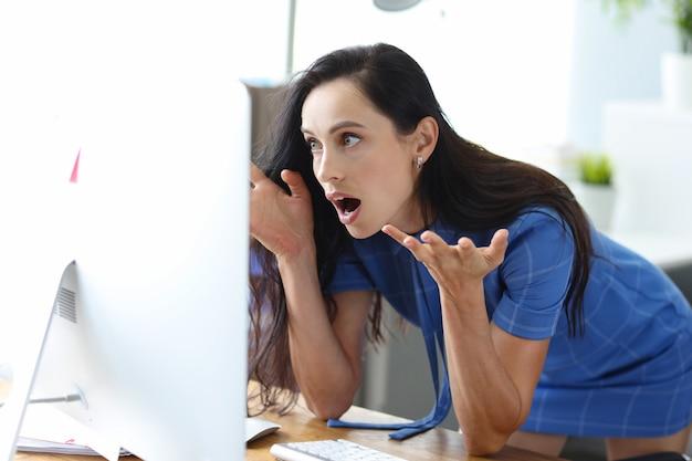 Mujer sorprendida se sienta a la mesa y mira la pantalla de la computadora con los ojos abiertos de par en par con horror en línea
