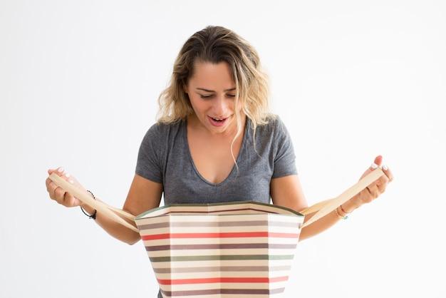 Mujer sorprendida sosteniendo el bolso de compras y mirando furtivamente en él