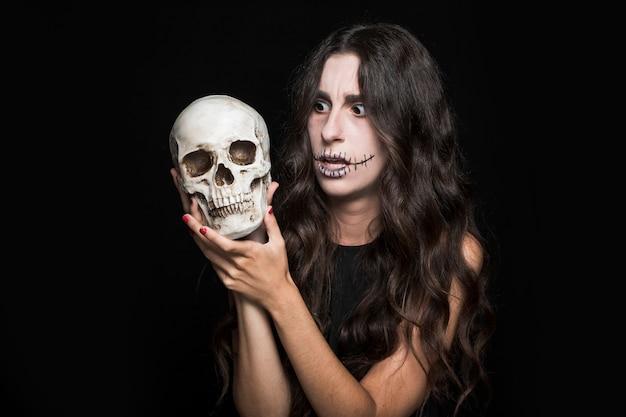 Mujer sorprendida sosteniendo el cráneo