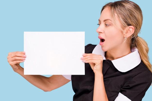 Mujer sorprendida sosteniendo y mirando el papel blanco en blanco de pie contra la pared azul