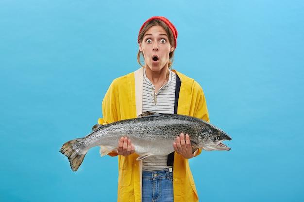 Mujer sorprendida sosteniendo un pez enorme que