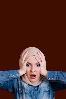 Mujer sorprendida sosteniendo su cabeza sobre superficie oscura