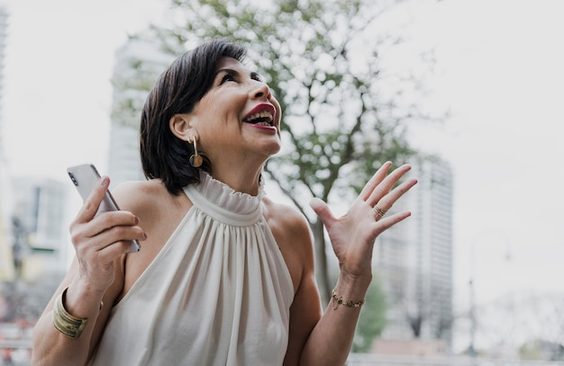 Mujer sorprendida sosteniendo un teléfono al aire libre