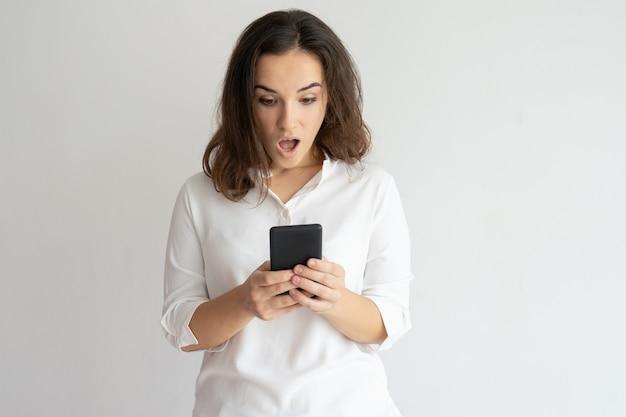 Mujer sorprendida sosteniendo teléfono inteligente y mirando su pantalla