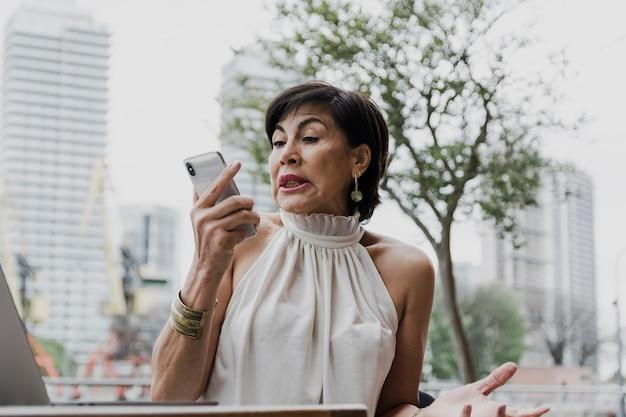 Mujer sorprendida sosteniendo un teléfono plano medio