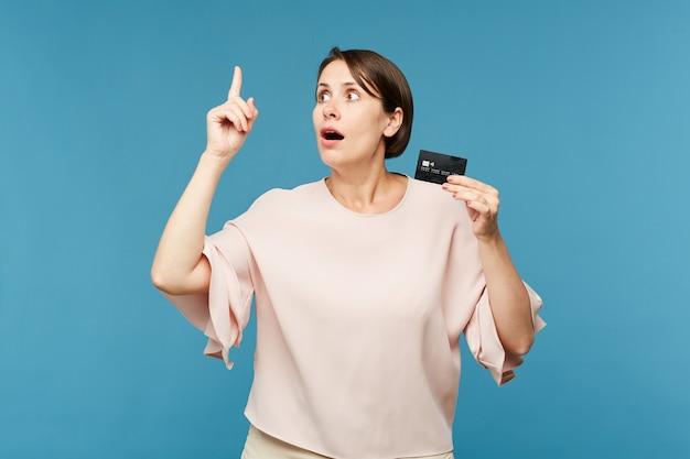 Mujer sorprendida con tarjeta de crédito negra en la pared azul