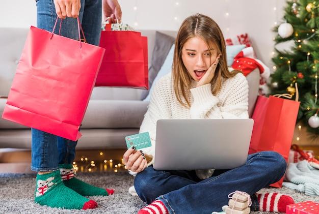 Mujer sorprendida con tarjeta de crédito y piernas de hombre.