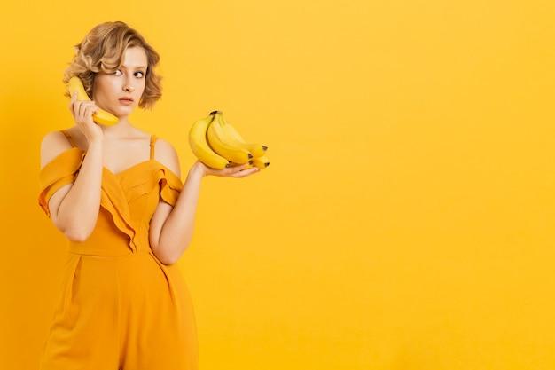 Mujer sorprendida usando banana como teléfono