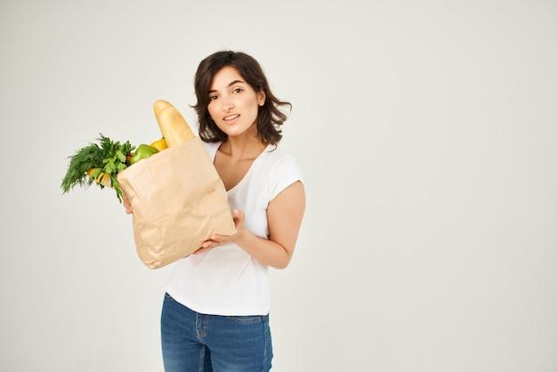 Mujer sosteniendo abarrotes entrega supermercado fondo claro