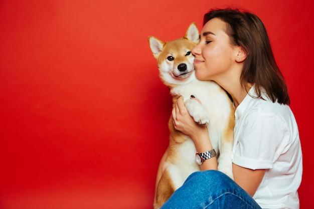 Mujer sosteniendo y abrazando el perro shiba inu