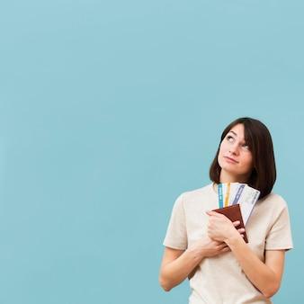 Mujer sosteniendo algunos boletos de avión con espacio de copia