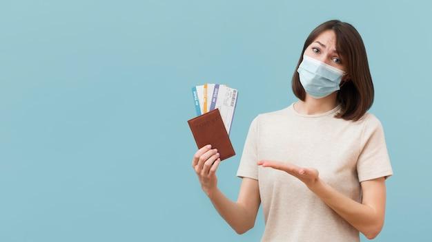 Mujer sosteniendo algunos boletos de avión mientras usa una máscara médica