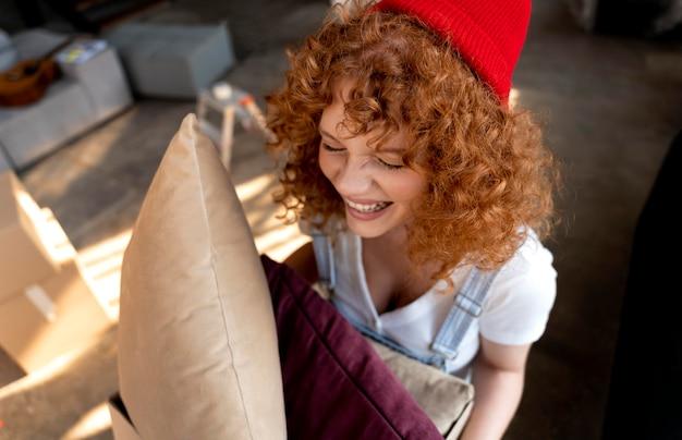 Mujer sosteniendo almohadas para decorar el nuevo hogar
