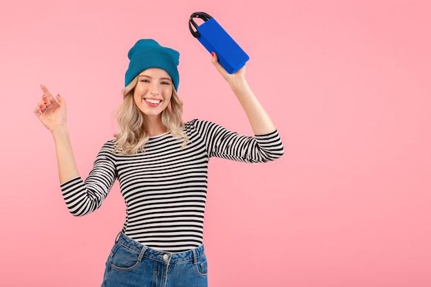 Mujer sosteniendo altavoz inalámbrico escuchando música vistiendo camisa a rayas y sombrero azul sonriendo feliz estado de ánimo positivo posando en rosa