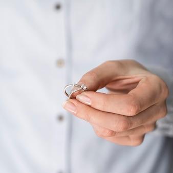 Mujer sosteniendo anillos de compromiso y matrimonio