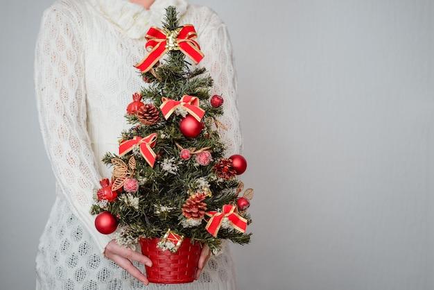 Mujer sosteniendo un árbol de navidad decorado con adornos rojos