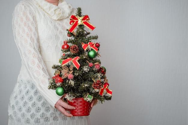 Mujer sosteniendo un árbol de navidad en la pared gris
