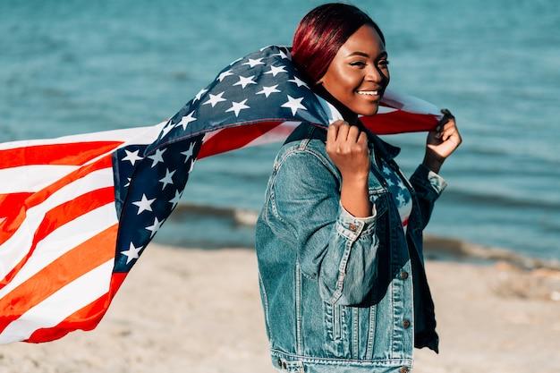 Mujer sosteniendo bandera estadounidense detrás de la espalda ondeando en el viento