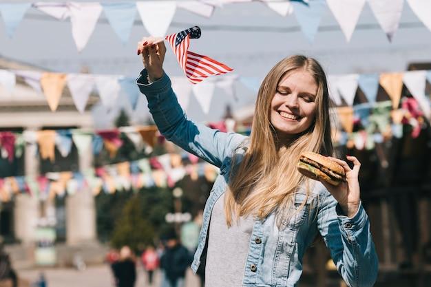 Mujer sosteniendo bandera estadounidense y hamburguesa sabrosa