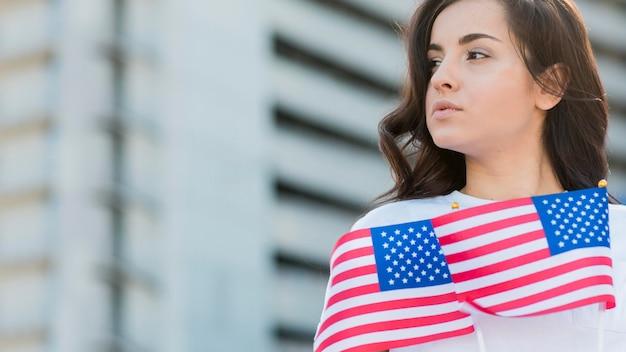 Mujer sosteniendo banderas de estados unidos mirando a otro lado