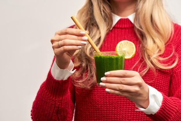 Mujer sosteniendo batido verde de espinacas frescas con paja de bambú