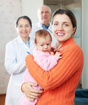 Mujer sosteniendo bebé con médicos