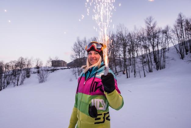 Mujer sosteniendo una bengala de fuegos artificiales